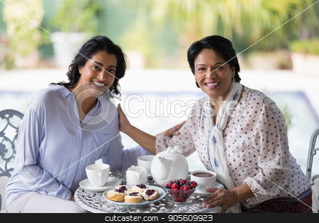 Portrait of woman having breakfast with mother stock photo, Portrait of woman having breakfast with mother at home by Wavebreak Media