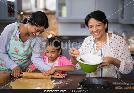 Portrait of woman preparing food with family in kitchen stock photo, Portrait of mature woman preparing food with family in kitchen at home by Wavebreak Media