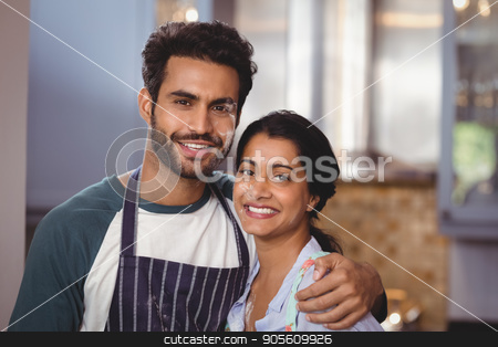 Portrait of smiling couple embracing in kitchen stock photo, Portrait of smiling young couple embracing in kitchen at home by Wavebreak Media