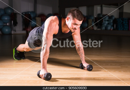 Young Man Athlete Doing Pushups With Dumbbells As Part Of Bodybuilding Training stock photo, Young Man Athlete Doing Pushups With Dumbbells As Part Of Bodybuilding Training by Satura86