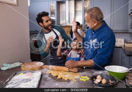 Happy multi-generation giving high five in kitchen stock photo, Happy multi-generation giving high five in kitchen at home by Wavebreak Media