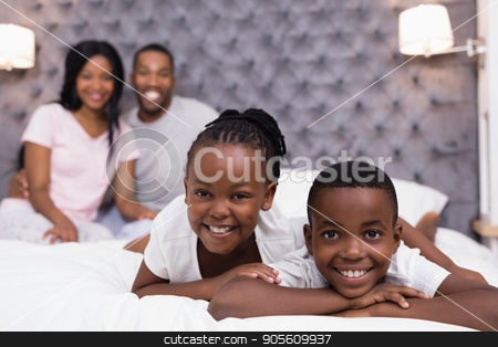 Portrait of siblings lying on bed with parents sitting in background stock photo, Portrait of smiling siblings lying on bed with parents sitting in background at home by Wavebreak Media