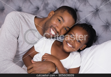 Portrait of man with daughter lying on bed stock photo, High angle portrait of man with daughter lying on bed at home by Wavebreak Media