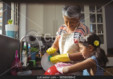 Grandmother and granddaughter washing utensil in kitchen sink stock photo, Grandmother and granddaughter washing utensil in kitchen sink at home by Wavebreak Media