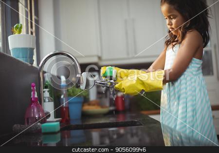 Cute little girl washing utensil in kitchen sink stock photo, Cute little girl washing utensil in kitchen sink at home by Wavebreak Media