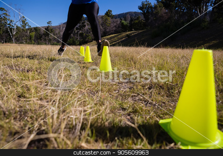 Low-section of woman running through training cones stock photo, Low-section of woman running through training cones on a sunny day by Wavebreak Media