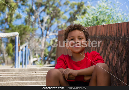 Boy sitting on staircase in the boot camp on a sunny day stock photo, Portrait of boy sitting on staircase in the boot camp on a sunny day by Wavebreak Media
