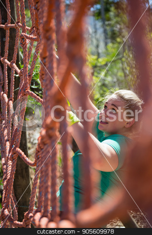 Determined woman climbing a net during obstacle course training stock photo, Determined woman climbing a net during obstacle course training in the boot camp by Wavebreak Media