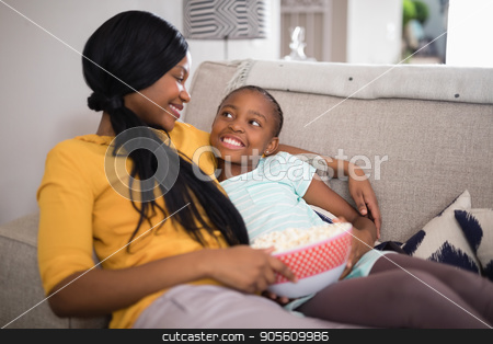 Mother and daughter having popcorn while resting on sofa at home stock photo, Smiling mother and daughter having popcorn while resting on sofa at home by Wavebreak Media