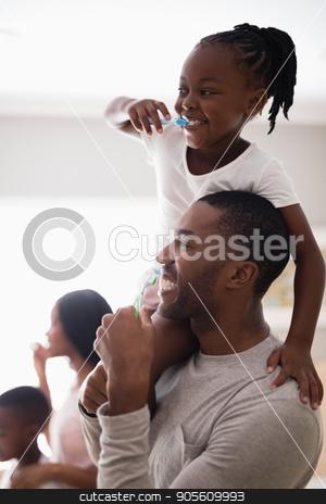 Happy family brushing teeth in bathroom stock photo, Happy family brushing teeth in bathroom at home by Wavebreak Media