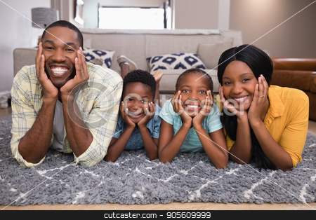 Portrait of smiling family lying on rug stock photo, Portrait of smiling family lying on rug at home by Wavebreak Media