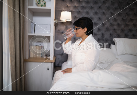 Mature woman drinking water while sitting on bed stock photo, Mature woman drinking water while sitting on bed at home by Wavebreak Media