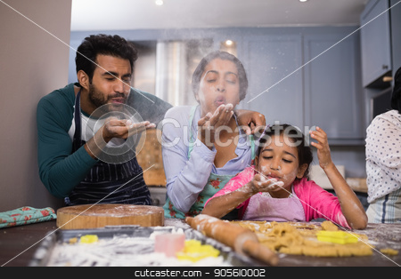 Playful family blowing flour in kitchen stock photo, Playful family blowing flour in kitchen at home by Wavebreak Media