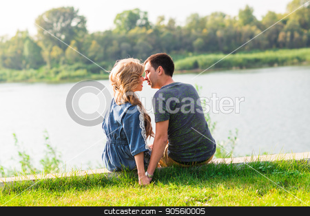 couple in love sitting near the summer lake shore stock photo, couple in love sitting near the summer lake shore by Satura86