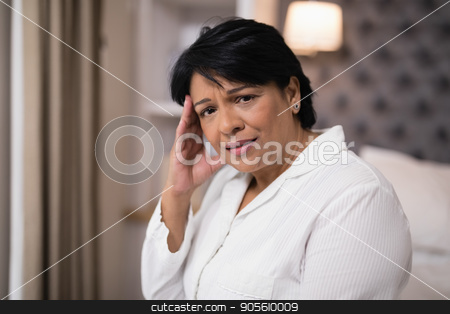 Mature woman suffering with headache at home stock photo, Portrait of mature woman suffering with headache at home by Wavebreak Media