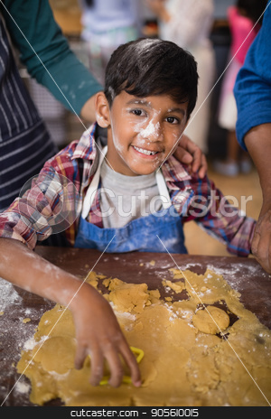 Portrait of smiling boy preparing food in kitchen stock photo, Portrait of smiling boy preparing food in kitchen at home by Wavebreak Media
