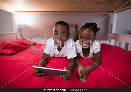 Happy siblings with digital tablet lying on bed at home stock photo, Portrait of happy siblings with digital tablet lying on bed at home by Wavebreak Media