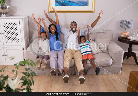 Happy family cheering while sitting on sofa at home stock photo, Portrait of happy family cheering while sitting on sofa at home by Wavebreak Media