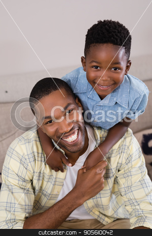 Cheerful father and son in living room at home stock photo, Portrait cheerful father and son in living room at home by Wavebreak Media