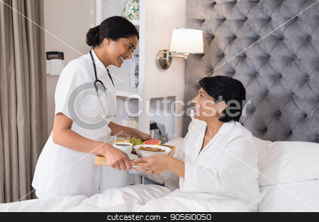 Smiling nurse serving breakfast to patient resting on bed stock photo, Smiling nurse serving breakfast to patient resting on bed at home by Wavebreak Media