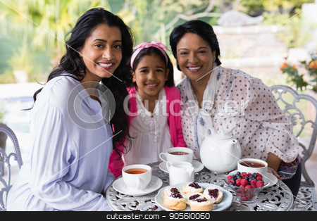 Portrait of smiling multi-generation family sitting together by breakfast table stock photo, Portrait of smiling multi-generation family sitting together by breakfast table at home by Wavebreak Media