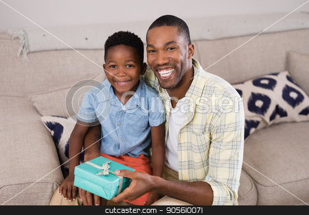 Smiling father and son with gift box sitting on sofa at home stock photo, Portrait of smiling father and son with gift box sitting on sofa at home by Wavebreak Media