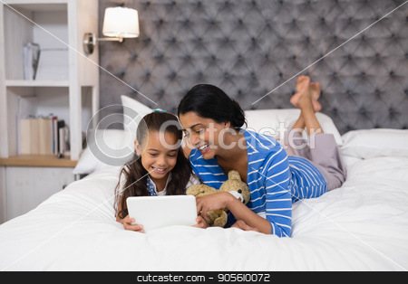 Mother and daughter using digital tablet while lying on bed at home stock photo, Smiling mother and daughter using digital tablet while lying on bed at home by Wavebreak Media