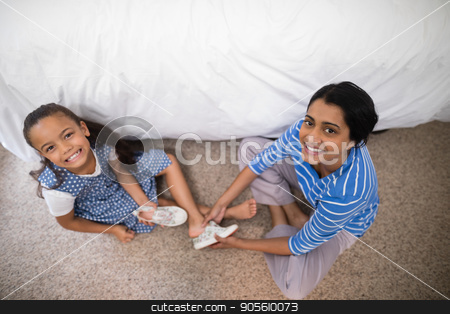 Portrait of mother helping daughter to wear shoe at home stock photo, High angle portrait of mother helping daughter to wear shoe at home by Wavebreak Media