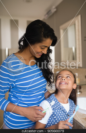 Girl with mother holding toothbrushes in bathroom stock photo, Smiling girl with mother holding toothbrushes in bathroom by Wavebreak Media