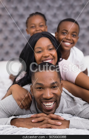 Portrait of smiling man with family lying on bed stock photo, Portrait of smiling man with family lying together on bed at home by Wavebreak Media