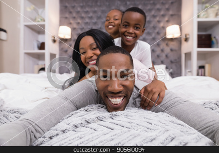 Portrait of happy man lying with family on bed stock photo, Portrait of happy man lying with family on bed at home by Wavebreak Media