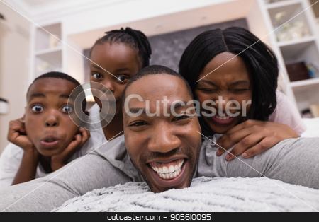 Portrait of happy family lying on bed stock photo, Portrait of happy family lying together on bed at home by Wavebreak Media