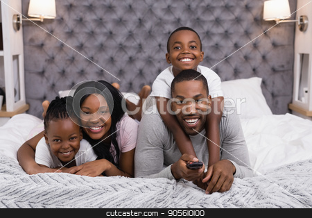 Portrait of happy family watching television while lying on bed stock photo, Portrait of happy family watching television while lying on bed at home by Wavebreak Media