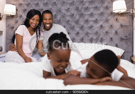 Happy couple sitting with children lying in foreground stock photo, Happy couple sitting on bed with children lying in foreground at home by Wavebreak Media