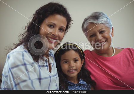 Happy family sitting on sofa in living room stock photo, Portrait of happy family sitting on sofa in living room at home by Wavebreak Media
