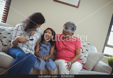 Smiling family watching television together in living room stock photo, Smiling family watching television together in living room at home by Wavebreak Media