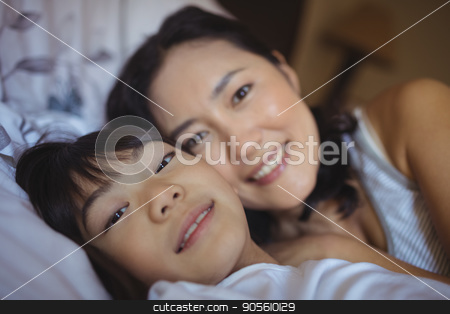 Mother and daughter relaxing on bed in bed room stock photo, Portrait of mother and daughter relaxing on bed in bed room at home by Wavebreak Media