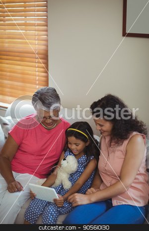 Happy family using digital tablet in living room stock photo, Happy family using digital tablet in living room at home by Wavebreak Media