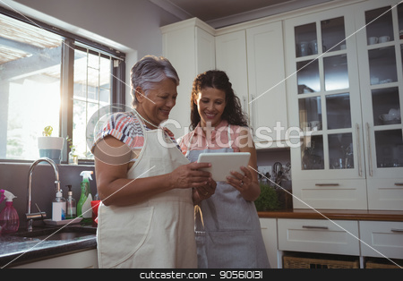 Mother and daughter using digital tablet in kitchen stock photo, Mother and daughter using digital tablet in kitchen at home by Wavebreak Media