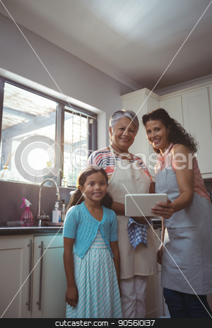 Happy family using digital tablet in kitchen stock photo, Happy family using digital tablet in kitchen at home by Wavebreak Media