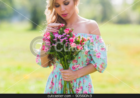 Close-up outdoor portrait of a beautiful blonde woman. attractive happy girl in a field with bouquet of flowers stock photo, outdoor portrait of a beautiful blonde woman. attractive happy girl in a field with bouquet of flowers by Satura86
