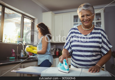 Mother ironing clothes while daughter washing utensil stock photo, Mother ironing clothes while daughter washing utensil at home by Wavebreak Media