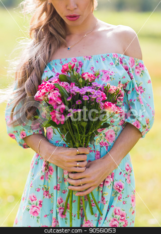 Close-up portrait of beautiful blonde girl holding bouquet of flowers at the countryside stock photo, Beautiful blonde girl holding bouquet of flowers at the countryside by Satura86