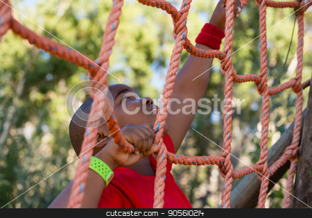 Boy climbing a net during obstacle course training stock photo, Boy climbing a net during obstacle course training in the boot camp by Wavebreak Media