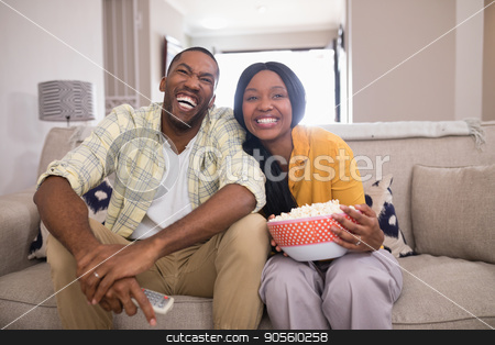 Cheerful young couple watching television while sitting on sofa at home stock photo, Cheerful young couple watching television while sitting on sofa at home by Wavebreak Media