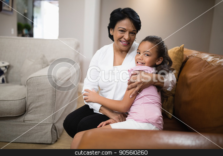 Portrait of grandmother and granddaughter embracing on sofa at home stock photo, Portrait of grandmother and granddaughter embracing while sitting on sofa at home by Wavebreak Media