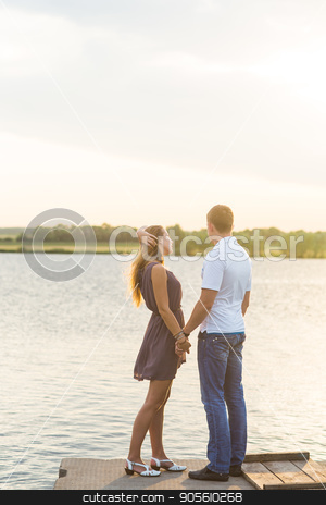 Young couple in love outdoors embracing at lake rear view stock photo, Young couple in love outdoors embracing at lake rear view by Satura86