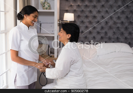 Smiling nurse comforting mature woman on bed stock photo, Smiling nurse comforting mature woman on bed at home by Wavebreak Media