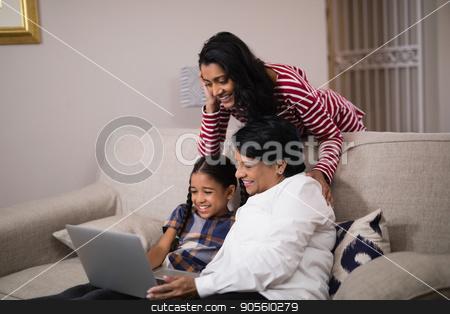 Happy multi-generation family using laptop together stock photo, Happy multi-generation family using laptop together at home by Wavebreak Media