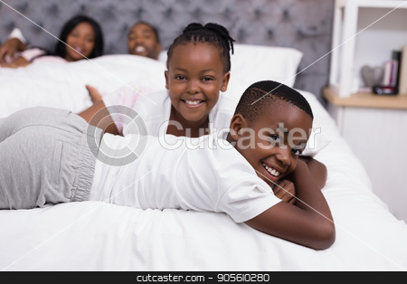 Portrait of smiling siblings lying with parents in background stock photo, Portrait of smiling siblings lying with parents in background on bed at home by Wavebreak Media